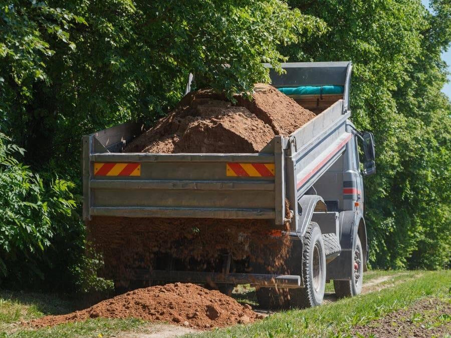 Dumper truck delivering topsoil