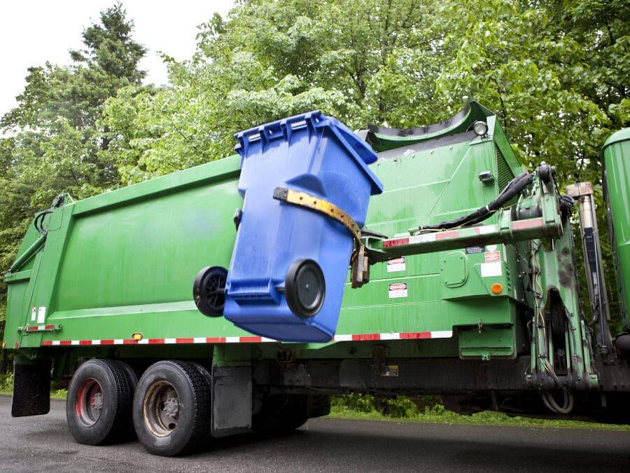 Green recycling lorry emptying recycle bin